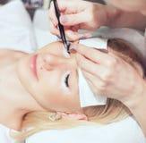 Kvinnan synar med långa ögonfranser Ögonfransförlängning Arkivbild