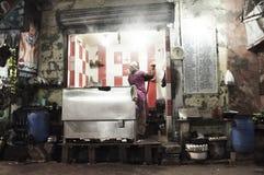 Kvinnan tänder rökelse i hennes kök för gatarestaurang` s på natten i Kolkata, Indien royaltyfri foto