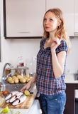 Kvinnan tänker vad för att laga mat fisken Royaltyfri Foto