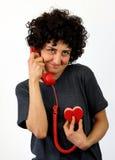 Kvinnan talar på den röda telefonen Arkivfoto
