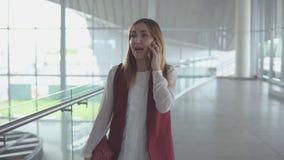 Kvinnan talar på smartphonen, medan stiga ombord på nivån arkivfilmer