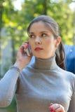 Kvinnan talar vid mobiltelefonen Royaltyfri Bild