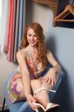 Kvinnan tar av skor Arkivbild