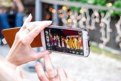 Kvinnan tar bilden med hennes mobiltelefon Arkivfoton