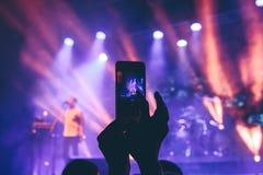 Kvinnan tar bilder på telefonen på en konsert Arkivbilder