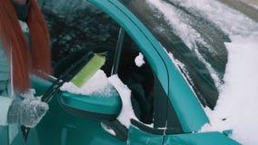 Kvinnan tar bort snö från bilen med borsten lager videofilmer