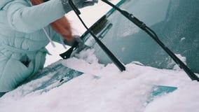 Kvinnan tar bort snö från vindrutan av bilen lager videofilmer