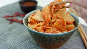 Kvinnan tar den traditionella koreanska kålaptitretaren Kimchi från den keramiska bunken med pinnar stock video