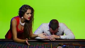 Kvinnan tar en man med kasinot, når han har förlorat alla chiper arkivfilmer