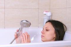 Kvinnan tar ett bad Hon häller hennes kroppvatten från duschen den täta dekorativa framsidan låter vara upp kanter den rosa treen arkivbilder