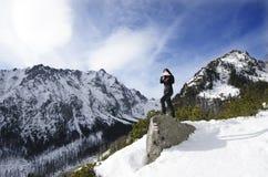 Kvinnan tar ett foto med mobilen, backgroung från berg fotografering för bildbyråer