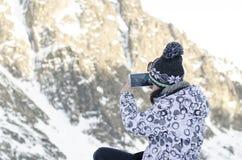 Kvinnan tar ett foto med mobilen, backgroung från berg arkivbild