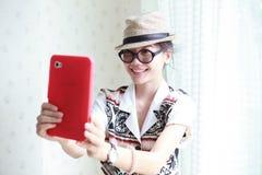 Kvinnan tar ett foto vid den smart telefontableten Arkivbild