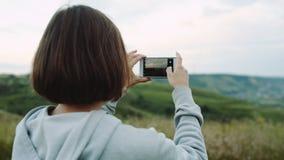 Kvinnan tar ett härligt landskap på kameratelefoner stock video