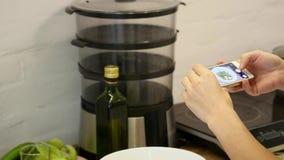 Kvinnan tar fotoet på den smarta telefonen och sätter i ramsidor av grön sallad och gurkan med den röda tomaten lager videofilmer