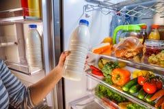 Kvinnan tar mjölka från det öppna kylskåpet Royaltyfria Bilder