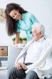 Kvinnan tar omsorg av patienten Arkivfoton