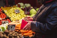 Kvinnan tar pengar ut från plånboken på marknad arkivbild