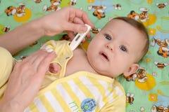 Kvinnan tar temperatur till det sjukt behandla som ett barn den elektroniska theren Royaltyfri Bild