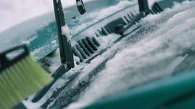 Kvinnan tar upp bort snö från vindrutan, slut arkivfilmer