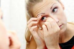 Kvinnan tar ut kontaktlinsen av hennes öga Arkivfoto