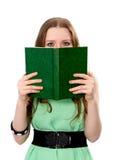 Kvinnan täcker hennes framsida med en bok Royaltyfri Bild