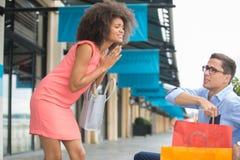 Kvinnan tigger pojkvännen för att fortsätta shopping Arkivbild