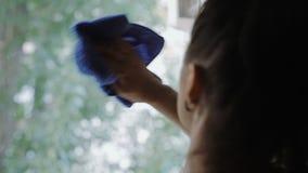 Kvinnan torkar fönstret med en blå trasa stock video