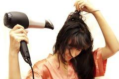 Kvinnan torkar hår hårtorken Royaltyfria Foton