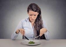 Kvinnan tröttade av bantar begränsningar som äter grön sallad Arkivbilder