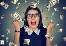 Kvinnan triumferar pumpa extatiska nävar firar framgång under pengarregn arkivbilder