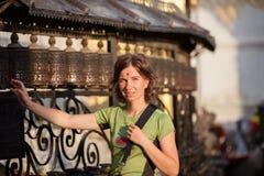 Kvinnan trycker på bönekvarnen i nepalese tempel Arkivbilder