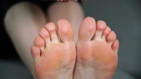 Kvinnan trycker på hennes fot, ben och anklar massage arkivfilmer