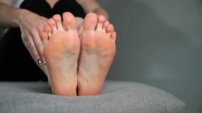 Kvinnan trycker på hennes fot, ben och anklar massage lager videofilmer