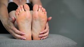 Kvinnan trycker på hennes fot, ben och anklar massage stock video