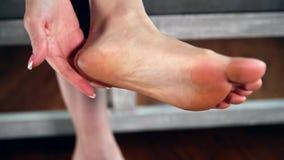 Kvinnan trycker på hennes fot, ben och anklar stock video