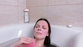 Kvinnan tvättar hennes framsida med en svamp från maskering och skurar att ligga i badrummet lager videofilmer