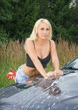 Kvinnan tvättar sportbilen Arkivbilder