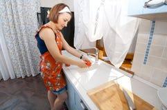 Kvinnan tvättar tomater Royaltyfri Foto