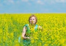 Kvinnan tycker om arom av gula blommor Arkivbild