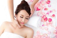 Kvinnan tycker om att motta framsidamassage på brunnsorten med rosor Royaltyfri Fotografi