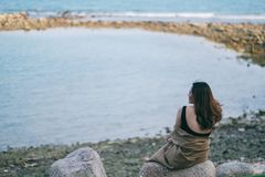 Kvinnan tycker om att sitta p? vaggar vid kusten arkivfoto