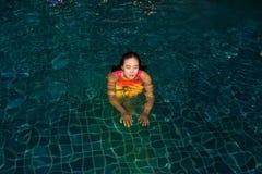 Kvinnan tycker om att spela hennes boll i simbassängen på natten i hotellet Royaltyfri Bild