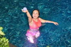 Kvinnan tycker om att spela hennes boll i simbassängen på natten i hotellet Royaltyfri Foto