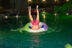 Kvinnan tycker om att spela hennes boll i simbassängen på natten i hotellet Arkivfoto