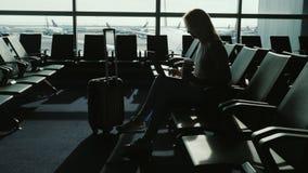 Kvinnan tycker om bärbara datorn och dricker kaffe på flygplatsterminalen Arkivbild
