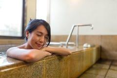 Kvinnan tycker om badet inomhus Royaltyfri Bild