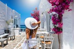 Kvinnan tycker om den klassiska inställningen av vita hus och färgrika blommor på de cyclades öarna av Grekland royaltyfri bild
