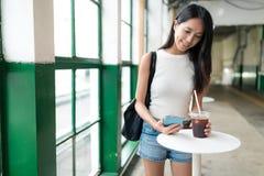 Kvinnan tycker om mobiltelefonen för med is kaffe och innehavi kafé för öppen luft royaltyfria foton