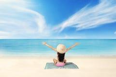 Kvinnan tycker om ny luft på kusten Arkivbild